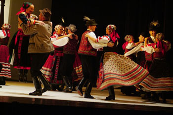 3-4 couples dancing on stage in Hungarian folk costume