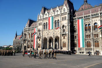 soldiers marching in front of the Parliament, that is decorate dwith the national flag