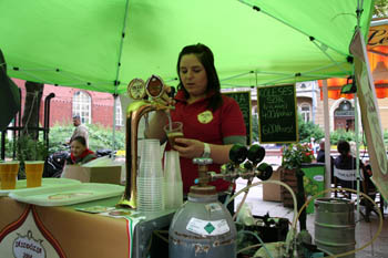 a young lady tapping beer into a plastic mug under a green tent