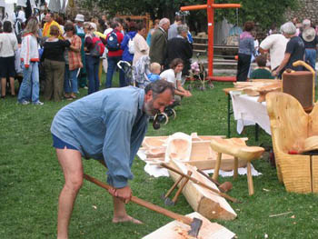 a middle-aged bearded man carving wood with an ax