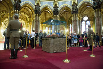 2 soldiers standing next to the Holy crown in a glass cabinet, visitors viewing the crown