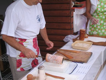 a man in white t-shirt and apron coating the pastry in sugar