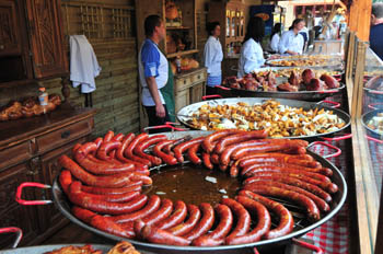 grilled sausages on a large, round metal plate