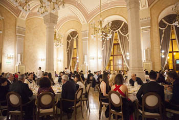 people having festive NYE dinner in an elegant arcaded dining hall