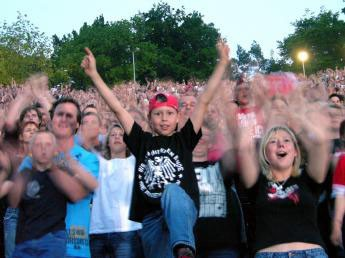 a kid in black t-shirt and red baseball cap among a crowd on a concert