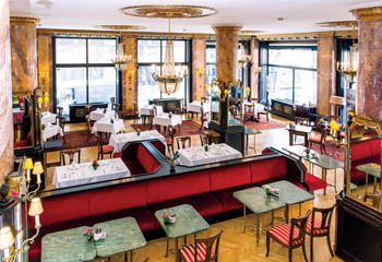 a black-topped bar with square green coffee tables, gilded chandelier huge panorama windows inside the cafe