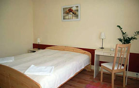 a room with a double bed, small table and chair in B and B hotel