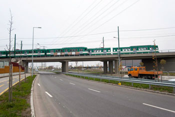 a green Suburban Railway on a flyover