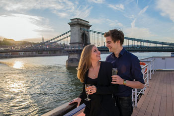 a young couple sipping wine on a boat on the Danube