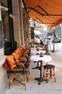 white clothed round tables under an orange tent on the terrace of the cafe