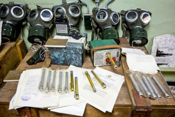 5 gas masks, papers, pens and other nicknacks on a table