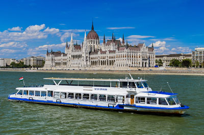 a white and blue cruise boat on the Danube with the Parliament in the background on a clear day