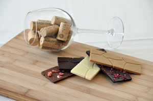 a couple of corks in a wine glass, with various square chocolates 8dark, white) in front of it