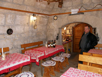 a couple of wooden tables with red table clotha in a vaulted stone cellar