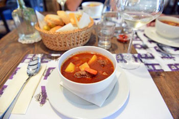 goulash in a round white bowl, slices of white bread in a small basket at a cellar