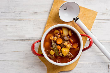 goulash soup in a red pot with a white ladle next to it on a wooden board
