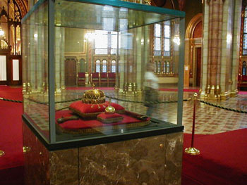 the crown on red pilow inside a glass cabinet