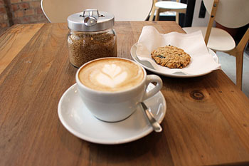 a cup of cappuccino with tulip latte art in a and a biscuit on a wooden table