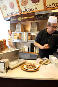 the owner, a middle-aged man wearing glasses and in white chef hat behind the counter