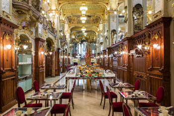 the richly decorated interior of the cafe: lots of gilded lamps, marble floor, mirrors tables in two rows