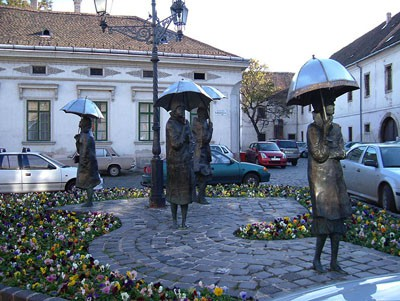 4 bronze statues of women with umbrella