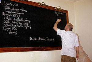 writing the menu on a black board Olimpia restaurant