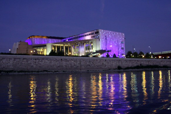 The Palace of Arts building illuminated in purple at night
