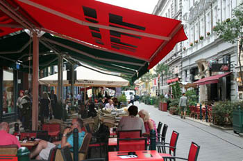 people eating on a terrace of a restaurant under a red tent