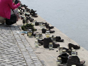"a woman in a pink jacket is taking photos of the ""shoe"" memorial"