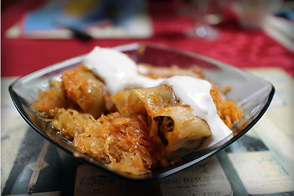 stuffed cabbage with sour cream in a square smoked glass bowl