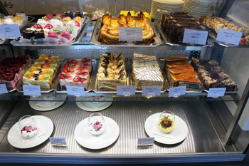 selection of cakes, pastries behind a glass counter