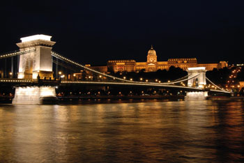 A cruise boat on the Danube at the lighted Chain bridge at night