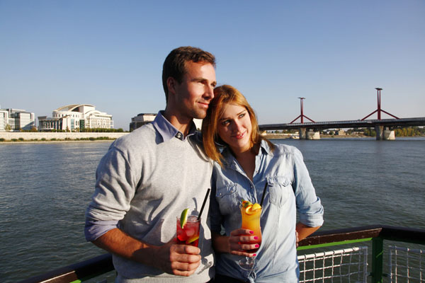 a romantic couple having a cocktail a river cruise in Budapest