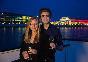 a young couple with a glass of wine in their hands on a cruise ship in Budapest