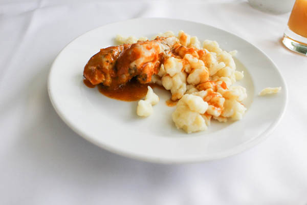 chicken paprikash with noodle son a round white plate