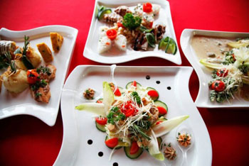 main dish, sides and salad on four white plates