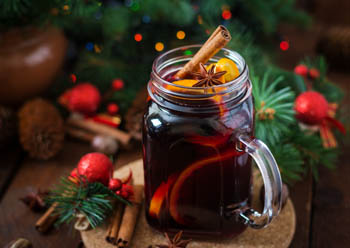 mulled red wine in a glass with a stick of cinnamon, anise and orange peels, Christmas decor in the background
