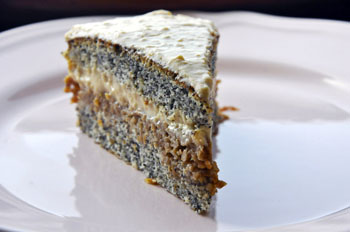 a slice of cake with layers of poppy seed sponge and stewed apple