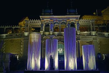 giant wood candles illuminated by purple light in front of the palace in Varkert