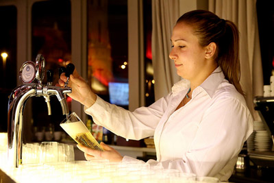 a bar tender woman drawing beer in a glass