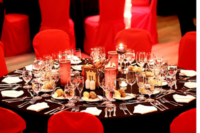 red chairs around a black clothed round table set for dinner