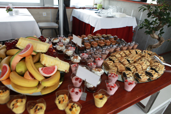 slices of cakes and various fruits (banana, melon ...) arranged nicely on the table