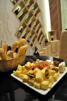 a cheese plate with ham and walnuts next to a basket of bakery goods