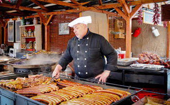 a man in a white chef hat grilling sausages