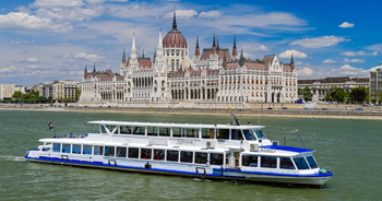 a white multi-deck ship on the Danube, the domed Royal Palace and the buildings of the Varkert in Buda in the background