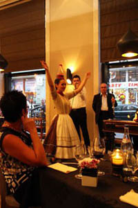 a young woman in folk costume doing a bottle dance in a restaurant