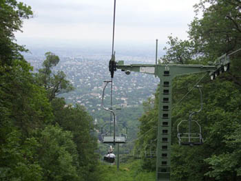 chairlift up on the hills with view of the green valley below