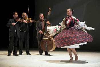 a young woman in red, sand black folk skirt and white blouse dancing, a 3-men band playing in the background