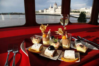 a couple of mini cakes and shot glass desserts on a plate, the Parliament and Danube through the window in the background