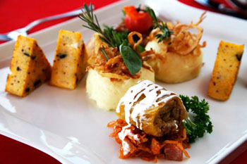 stuffed cabbage and grilled polenta slices on a white square plate